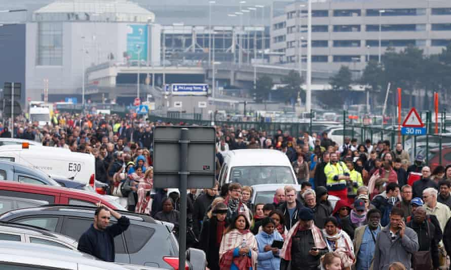 Passengers and airport staff are evacuated from the terminal building after Tuesday's explosions