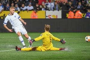Finland's Jasse Tuominen slots the ball past goalkeeper Benjamin Buchel of Liechtenstein for the opening goal.