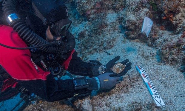 A diver holds a bronze disc discovered during the 2017 underwater excavations at Antikythera, Greece