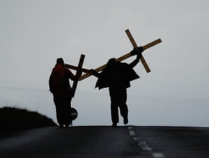 Pilgrims bearing wooden crosses cross the tidal causeway on the final stage of their annual pilgrimage to the Holy Island of Lindisfarne in Berwick-upon-Tweed, England.
