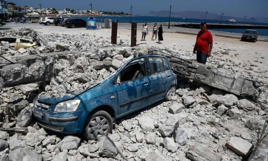 A man looks at a car crushed under rubble near the port in Kos
