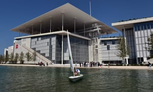 A man sails in front of the newly built Athens national Opera and library buildings at the Stavros Niarchos Cultural Center in Athens, Greece.