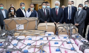 From right to left in front row, Iran's Ambassador to Lebanon Mohammed Jalal Feiruznia, Lebanese Health Minister Hamad Hassan, Lebanese Foreign Minister Nassif Hitti, and Minister of Public Works and Transportation Michel Najjar, stand next to coronavirus aid supplies delivered by the Iranian government at the Rafik Hariri International Airport in Beirut, Lebanon, Monday, 4 May 2020.