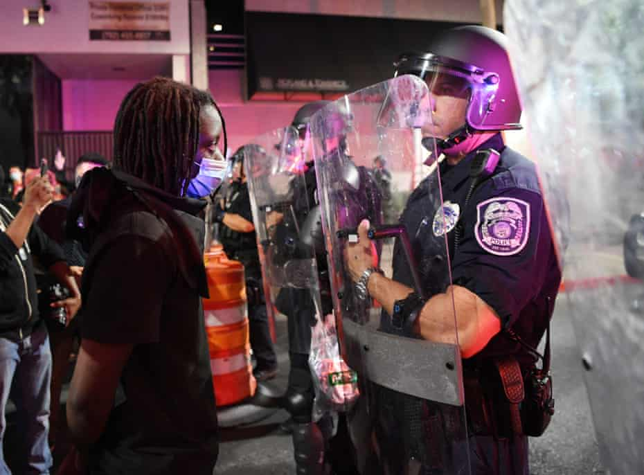 A protester in Las Vegas stands in front of a police officer during a demonstration demanding justice for the death of George Floyd.
