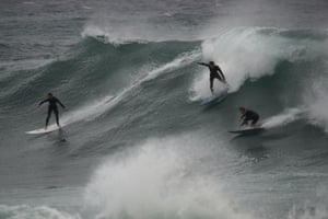 Surfers ride unusually large waves produced by swells hitting the coast at Bronte Beach.