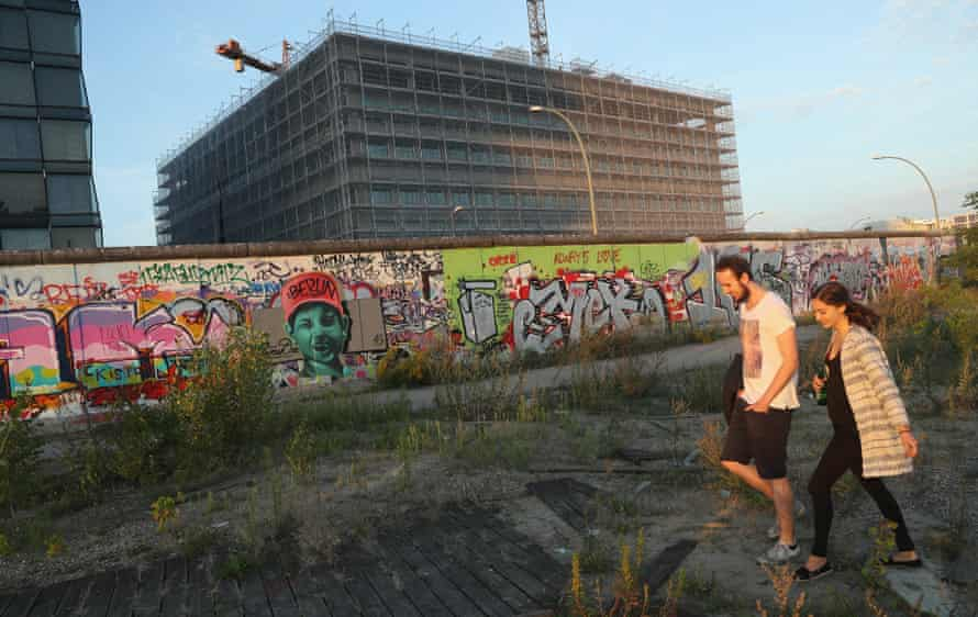 A couple walks past emnants of the Berlin Wall.