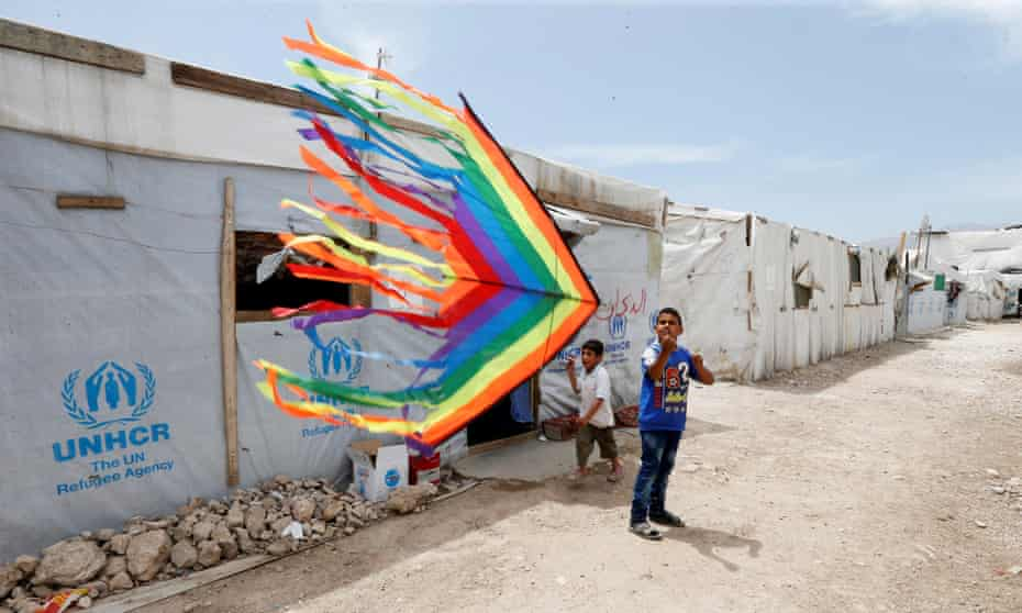 Syrian refugee boys fly a kite inside a Syrian refugee camp in Bekaa valley, Lebanon