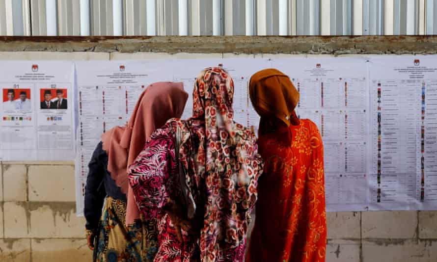 Women look at voting information at a polling station during elections in Bogor, West Java, Indonesia.