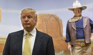 Donald Trump with a statue of actor John Wayne while campaigning in Iowa in 2015.