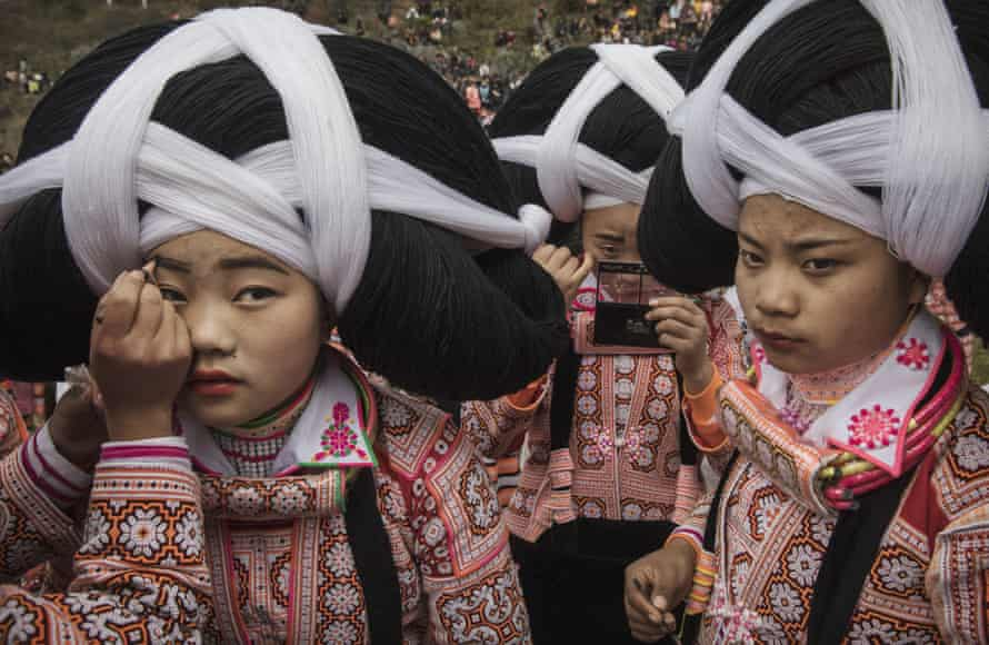 A teenage girl from the Long Horn Miao ethnic group has makeup applied as she and her friends prepare to celebrate tiaohua (flower) festival. The event is part of lunar new year festivities in Longga village, Guizhou province, southern China