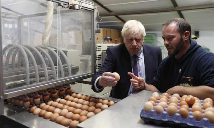 Boris Johnson examines eggs at a farm near Newport, south Wales, in July.