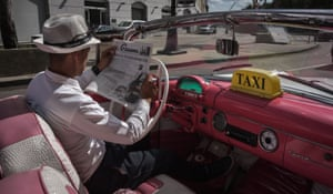 A taxi driver reads the newspaper