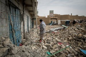 A representative of the Houthi rebels surveys the rubble of a recent airstrike on Sa'dah's old market