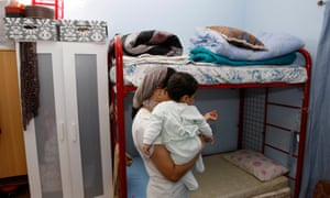 An Uzbek woman stands in her bedroom at the City of Hope women's shelter in Dubai.