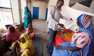 A doctor assists a baby with critical malnutrition in El Sereif hospital, North Darfur