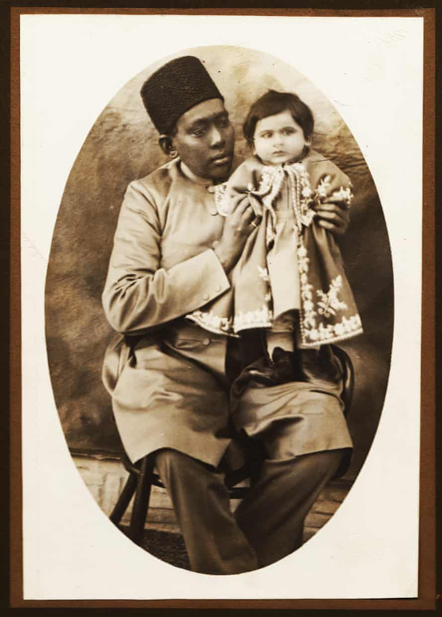 Based on the captions of other photos from the same album written by Masoud Mirza Zell-e-Soltan, the photographer of this image is Zell-e-Soltan himself and the baby in the picture a granddaughter, probably Nim Taj Khanum (Lady Nim Taj), with her African slave, in Isfahan, 1890s. During the Qajar period babysitting and accompanying royal and aristocratic children to their classes were among the main duties of African slaves.
