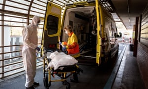 A worker from the emergency health service disinfects a stretcher after transferring a possible case of Covid-19 at a hospital in Catalonia. At the end of the service they disinfect and throw the personal protective equipment in G-II bags to avoid contagions.
