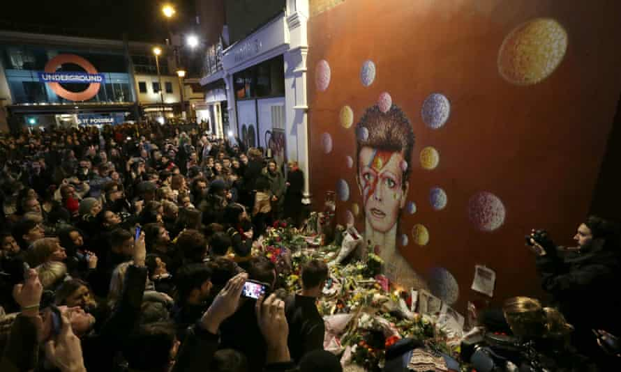People gather next to tributes left near the mural of David Bowie in Brixton, south London.