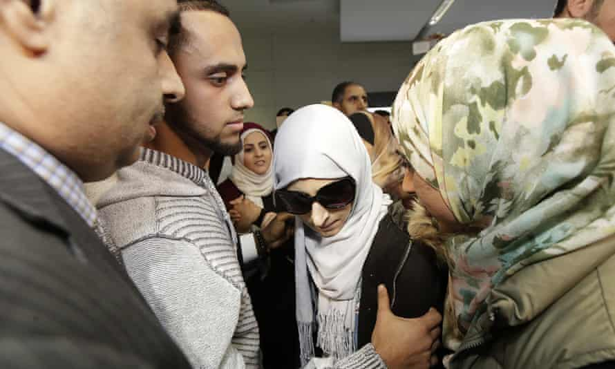 Shaima Swileh (centre) stands with her husband, Ali Hassan, second from left, after arriving at San Francisco airport