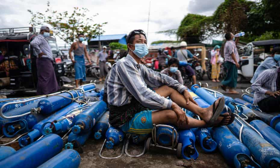 A man sits on empty oxygen canisters, as he waits to fill them up, outside a factory in Mandalay amid a surge in Covid-19 coronavirus cases in Myanmar