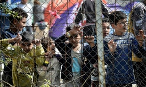Children stand behind a fence inside the Moria migration camp in Mytilene, the capital of Lesbos