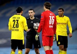 Referee Ovidiu Alin Hategan speaks to Borussia Dortmund's Emre Can after consulting VAR.