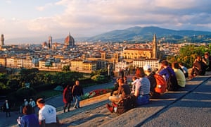 Tourists resting on steps at Piazzale Michelangelo above Florence's Arno river at sunset