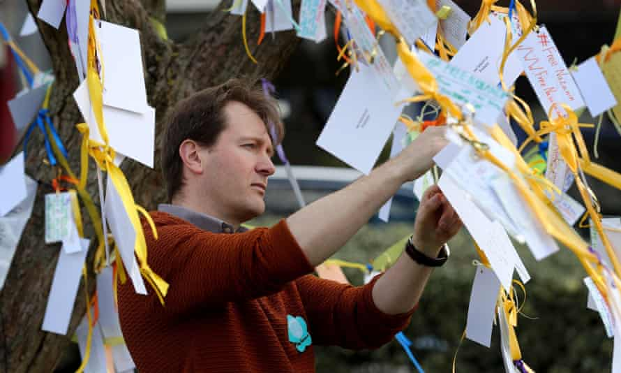 Richard Ratcliffe ties ribbons and messages of support to a tree to mark 365 days since his wife, Nazanin, was jailed.