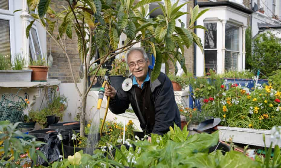 Hasam, who has lived on Evering Road for 35 years, surrounded by plants in his garden.