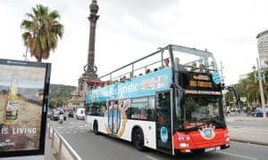 Visitors ride on a tourist bus past the Colombus monument in Barcelona
