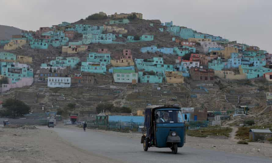 A rickshaw next to a hill of brightly painted homes in Kabul.