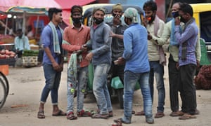 Daily wage labourers wearing face masks as a precaution against the coronavirus stand together as they wait for work at a wholesale market in Bengaluru, India, Thursday, 24 September 2020.