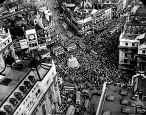 A crowd gathers to celebrate VE Day at Piccadilly Circus in London. The statue of Eros in the centre of the square has been boarded up throughout the war for protection from bombing