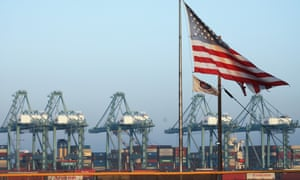 An American flag flies with shipping containers stacked at the Port of Los Angeles, which is the nation's busiest container port, on November 7, 2019 in San Pedro, California. Port officials said today October cargo volume was down 19% this year compared with October 2018 due to tariffs imposed in the US-China trade war.