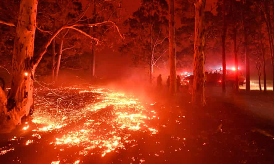 Burning embers cover the ground as firefighters battle against bushfires around the town of Nowra, New South Wales on December 31, 2019.