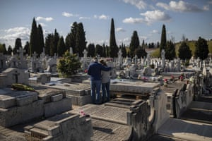 Madrid, Spain Two mourners attend the burial of a relative at a Madrid cemetery