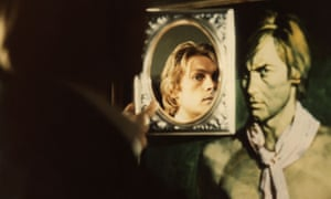 Helmut Berger as Dorian Gray, holding a mirror and seeing a younger man