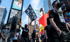 Protester supporting Hong Kong's pro-democracy movement wearing protective mask holds a flag as they attend the Delay No More, Democracy march in Times Square