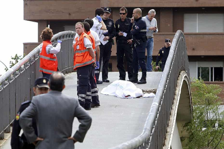 Police stand next to the body of Isabel Carrasco at the crime scene.