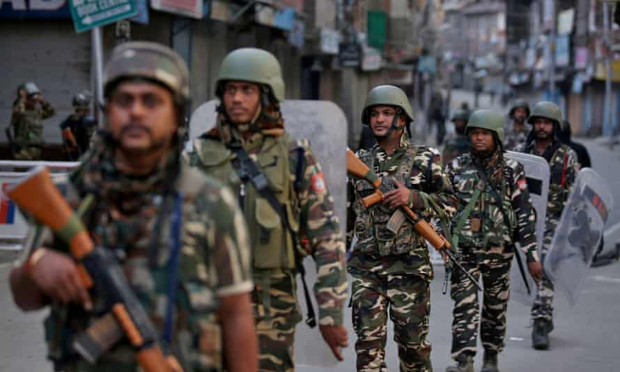 Indian security forces personnel patrol a deserted street during restrictions after the government scrapped special status for Kashmir, in an August photo.