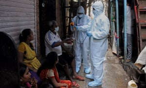 A healthcare worker checks the body temperature of a man in Dharavi, Asia's largest slum colony, last month.