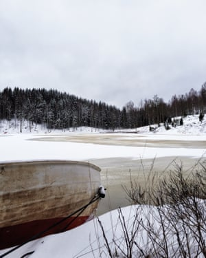 Landscape image of Dalsland, Sweden, in winter. In the foreground a boat wedged on the land, in the background bare trees and snow.