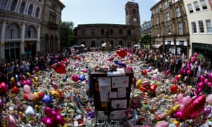 People look at floral tributes for the victims of the Manchester Arena attack, in St Ann's Square, in central Manchester