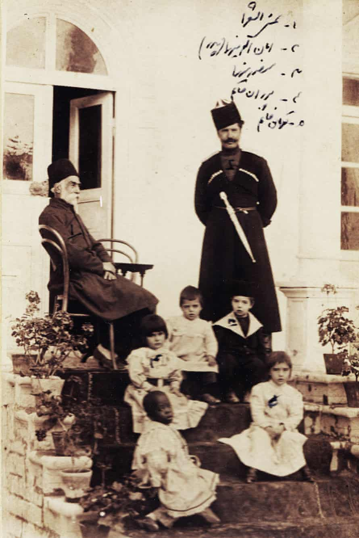 Shams al-Sho'ara (Abdulhossein Mirza Shams Molkara), seated, his son-in-law Amanullah Mirza Jahanbani (1869-1912) standing on the right, small boy wearing a hat (Mansour Mirza Jahanbani), other boy Azizollah, two little girls (Pouran Khanom Jahanbani, Touran Khanom Jahanbani), and an African slave girl, 1900s.