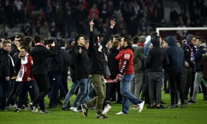 Lille fans invade the pitch after their 1-1 draw against Montpellier.