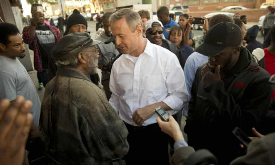 The former Maryland governor Martin O'Malley, centre, meets residents of Baltimore last week.