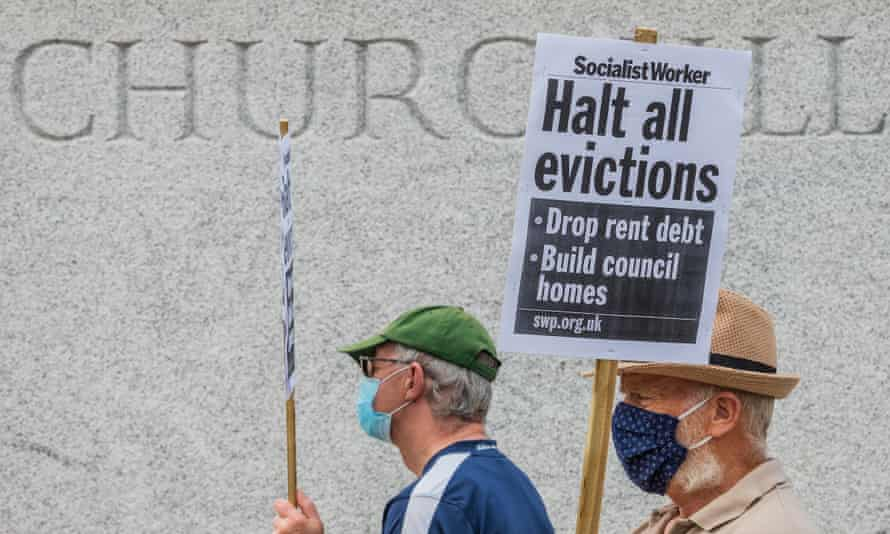 """Two men in masks walking past the base of Churchill's statue , one holding a placard saying """"Halt all evictions"""""""