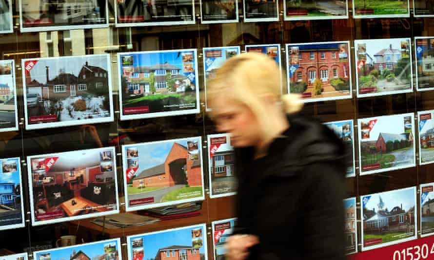Young woman walking past an estate agent's window