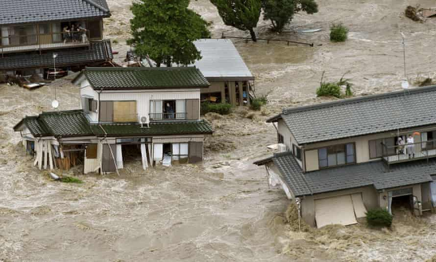People wait to be rescued as floodwaters engulf their homes