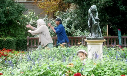 A child hides amongst the flowers as men practice Tai Chi in a London park.